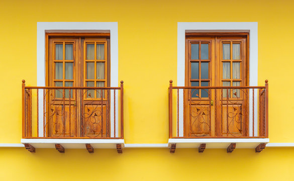 Two colonial style lemon yellow balconies with wooden framework and decorations in the historic city center of Cuenca, Ecuador.