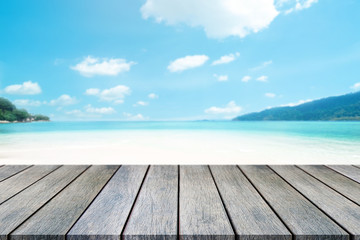 Perspective wooden table on top over blur sea in sunny day background. Beautiful sea and clouds in Thailand on summer, can be used mock up for montage products display or design layout.
