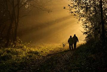 dwie osoby z psem na jesiennym spacerze