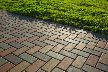 Colorful cobblestone road pavement and lawn divided by a concrete curb. Backlight.