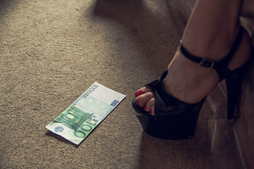 women's feet in shoes next to the money. photos of women's legs in strips Euro dollars beautiful photo of women's legs with money