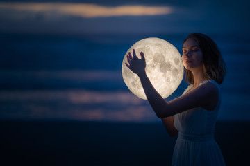 Tender image of a girl. Female magic. Beautiful attractive girl on a night beach with sand hugs the moon, art photo. On a dark background with space. Riddle, astrology, zodiac. Banner.