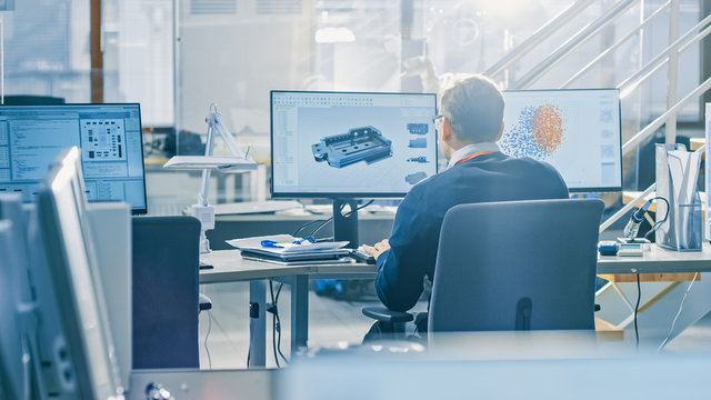 Back View of Industrial Engineer Working on Desktop Computer in Bright Office. Screens Show IDE / CAD Software, Implementation of Machine Learning, Neural Networking and Cloud Computing