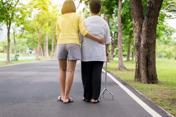 Elderly Asian female walking to do physical with stick at park,Daughter take care and support Wall mural