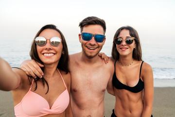 Young friends hugging taking selfie on ocean seashore beach together