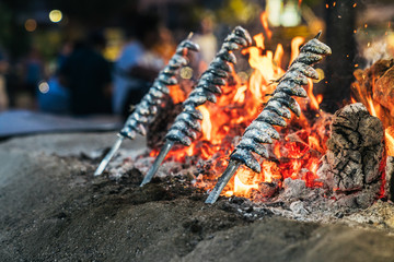 Skewers of small fish on open fire