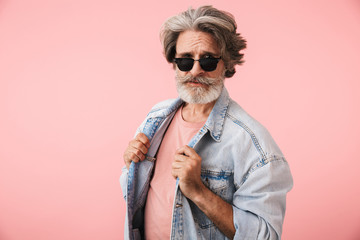 Portrait of fashion old man with gray beard wearing sunglasses and denim jacket looking at camera