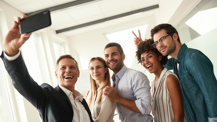 Happy moments. Group of smiling colleagues taking selfie and gesturing while standing in the modern office