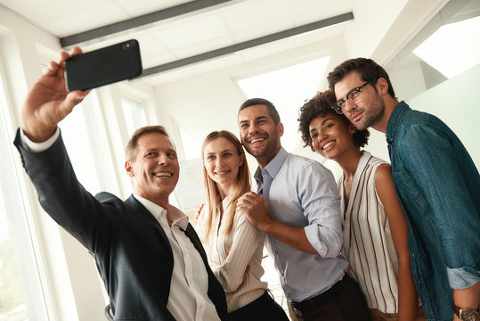 Happy team Group of smiling colleagues taking selfie while standing in the modern office