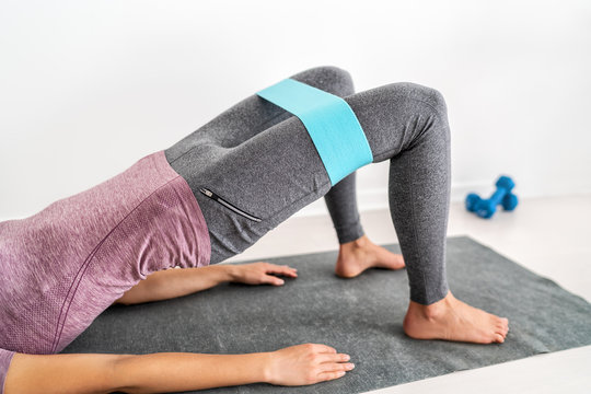 Fitness resistance band loop around thighs - booty band circle hip bands exercise for glute hip bridge abduction. Yoga fit girl strength training on floor at gym.