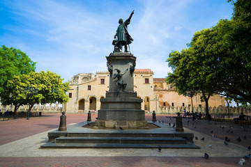Statue of Columbus in Parque Colon - central square of historic district of Santo Domingo, Dominican Republic. The oldest cathedral in the Americas in the background.