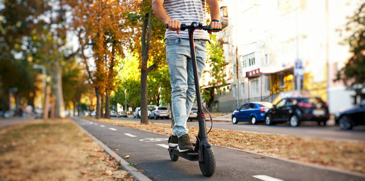 The young man is riding on the electric scooter through the evening city by the pathways