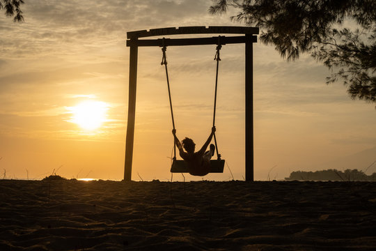 Girl swinging on swing, silhouette by sunset, sunrise, beach, sky dreamy travel photo