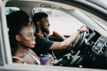 Leisure, road trip, travel, family and people concept - African happy man and woman driving in car with coffee