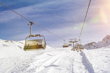 Chairlift in a ski resort in winter with scenic lens flare
