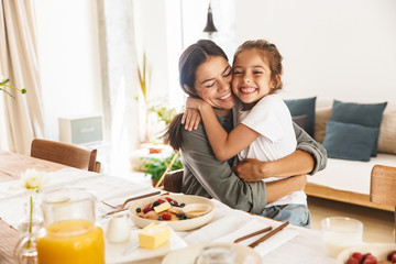 Image of happy family mother and little daughter hugging while having breakfast at home in morning