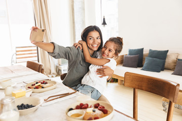 Image of beautiful family mother and little daughter taking selfie photo while having breakfast at home in morning