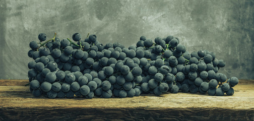 Beautiful wine grapes  on a old oak wooden table and gray background.