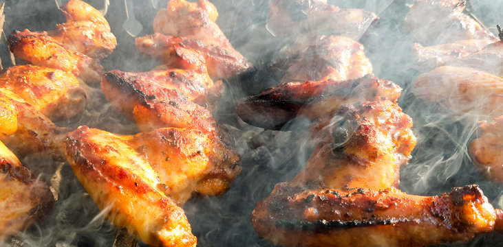 Delicious juicy grilled chicken wings outdoors in smoke. BBQ Chicken Cooking Process