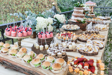 Table decorated with desserts, snacks and cake - wedding reception for event guests.