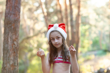 A child is playing with a santa claus hat. Happy little girl in Santa Claus hat outdoors in summer .