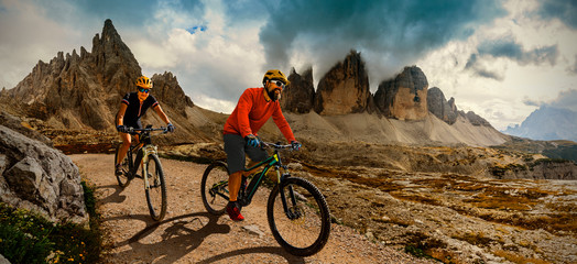 Wall Mural - Couple cycling on electric bike, rides mountain trail. Woman and Man riding on bikes in Dolomites mountains landscape. Cycling e-mtb enduro trail track. Outdoor sport activity.