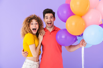 Cheerful young couple standing isolated over violet