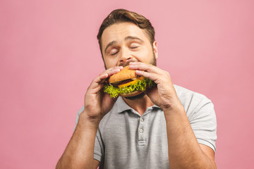 Foto op Aluminium Kruidenierswinkel Young man holding a piece of hamburger. Bearded gyu eats fast food. Burger is not helpful food. Very hungry guy. Diet concept. Isolated over pink background.
