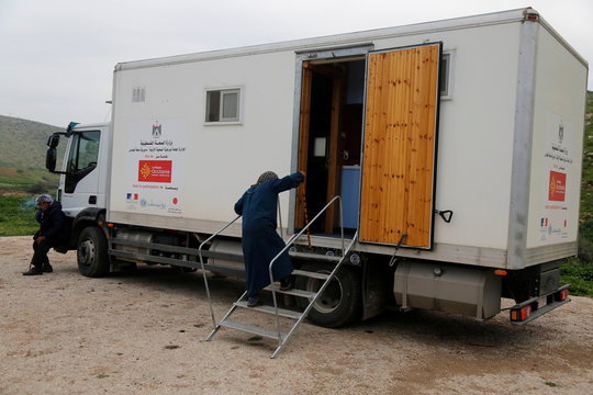 Palestinian woman arrives for medical checks in a mobile clinic, in the Bedouin village of Al-Maleh in Jordan valley in the Israeli-occupied West Bank