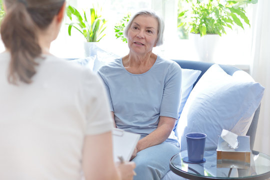Talk therapy concept: female doctor talking with her senior patient about her problems during a counseling session.