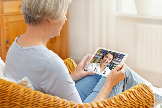 telemedicine concept, old woman with tablet pc during an online consultation with her doctor in her living room