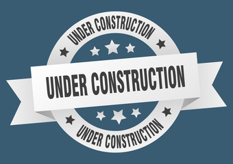 under construction ribbon. under construction round white sign. under construction