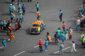 People look at a car painted with the 'Estelada' (Catalan separatist flag) before the rally during Catalonia's national day 'La Diada' in Barcelona