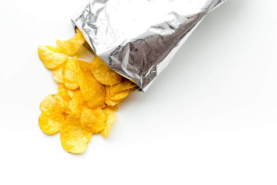 Bag of homemade potato chips for snack on white background top view copyspace
