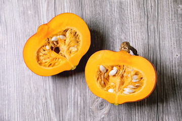 Two halves of raw organic hokkaido pumpkin with seeds over grey wooden background. Flat lay, space