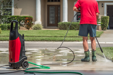 Man using electric powered pressure washer to power wash residential concrete driveway.