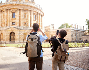 Male Gay Couple On Vacation Taking Photos Of Radcliffe Camera Building In Oxford On Mobile Phones