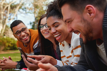 group of multi ethnic friends in college lying together in the park enjoying watching text or video on mobile phone - smiling group of students
