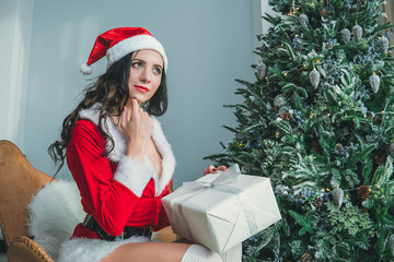 Portrait beautiful girl with long hair with box present and christmas hat. Thoughtful face girl. Dream of a good Christmas gift. Girl thinks. new year's dreams and hopes.