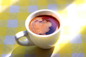 Cup of foamy morning coffee on a yellow tablecloth in the sunlight.