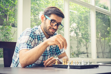Casual businessman playing chess game with retro style photo, in business competition and planning strategies concept.