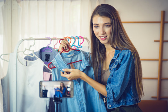 Young girl selling clothes online by live streaming from mobile phone.