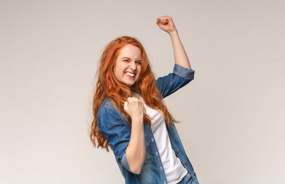 Millennial Girl Shaking Fists Celebrating Success On Light Studio Background