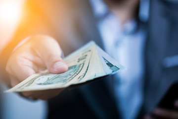 Businessman holding USD banknote for payment.US dollar is main and popular currency of exchange in the world. Investment and saving concept.