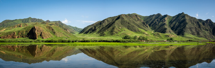 China landscape panorama. Sangke grassland close to Xiahe, Gansu, China. Beautiful mountain reflections at the wetlands of Gannan.