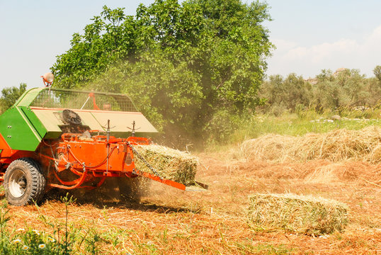 Machine for harvesting form square bales of hay.