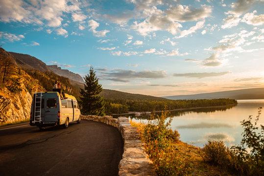 Women enjoying camper van with a view of a lake