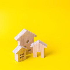 Three houses on a yellow background. Buying and selling of real estate, construction. Apartments...