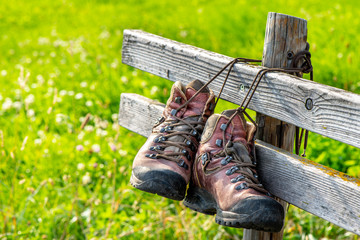Wanderschuhe hängen bei Rast an Holzbank