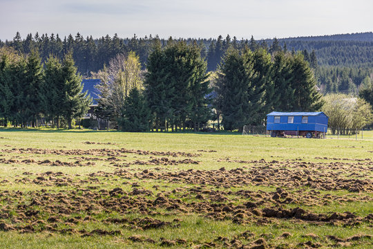 Blue mobile trailer home parked in a rural field with rough tussocks of grass possible due to moles and woodland trees and forested hills in the background